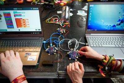 Zwei aufgeklappte Laptops, dazwischen spielen Kinderhände mit zwei sternförmigen Mikrocontrollern, den Calliope Minis