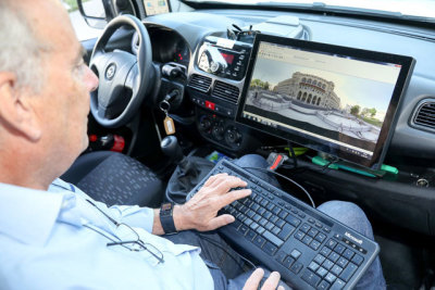 Mann auf Beifahrersitz mit Tastatur und Bildschirm
